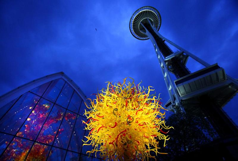 """In this May 16, 2012 photo, the Space Needle towers over """"The Sun,"""" center, and the Glasshouse, left, at the new Dale Chihuly Garden and Glass museum at the Seattle Center. Fifty years after the World's Fair inserted the Space Needle into Seattle's skyline, the city is celebrating that anniversary by offering an array of new things to see and do at Seattle Center: from a zip line to the new art glass museum.(AP Photo/seattlepi.com, Joshua Trujillo) MAGS OUT; NO SALES; SEATTLE TIMES OUT; MANDATORY CREDIT; TV OUT"""