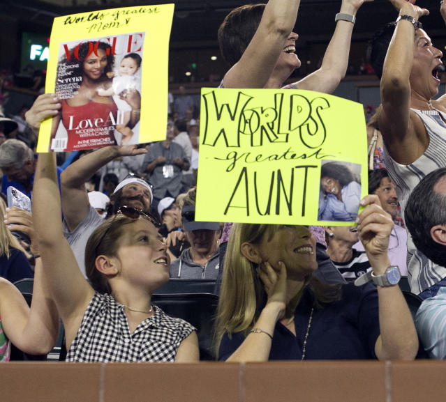 Ellie Sullivan, 10, of Dallas, left, and her mother, Andrea Sullivan, hold up signs for Serena and Venus Williams during a break as the sisters face one another in the third round of the BNP Paribas Open tennis tournament at the Indian Wells Tennis Garden in Indian Wells, Calif., Monday, March 12, 2018. (AP Photo/Crystal Chatham)