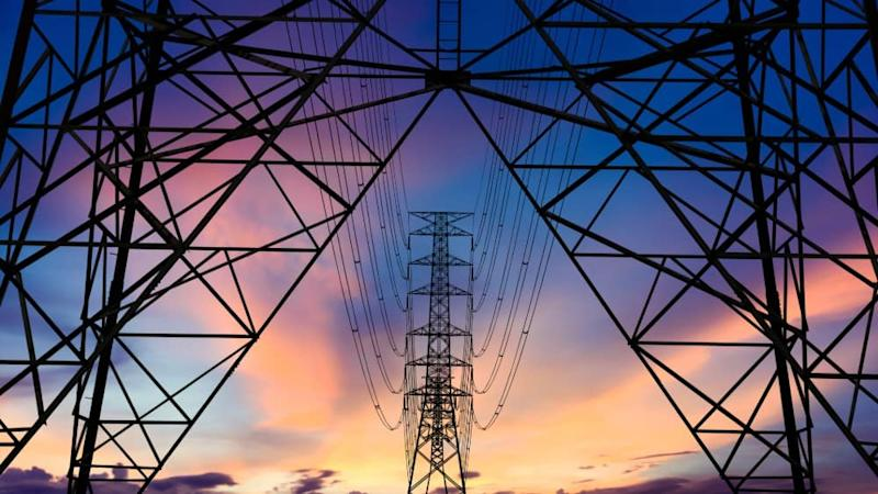 Electricity pylons against a sunset