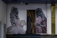 An Afghan woman enters a beauty salon in Kabul, Afghanistan, Saturday, Sept. 11, 2021. Since the Taliban gained control of Kabul, several images depicting women outside beauty salons have been removed or covered up. (AP Photo/Bernat Armangue)