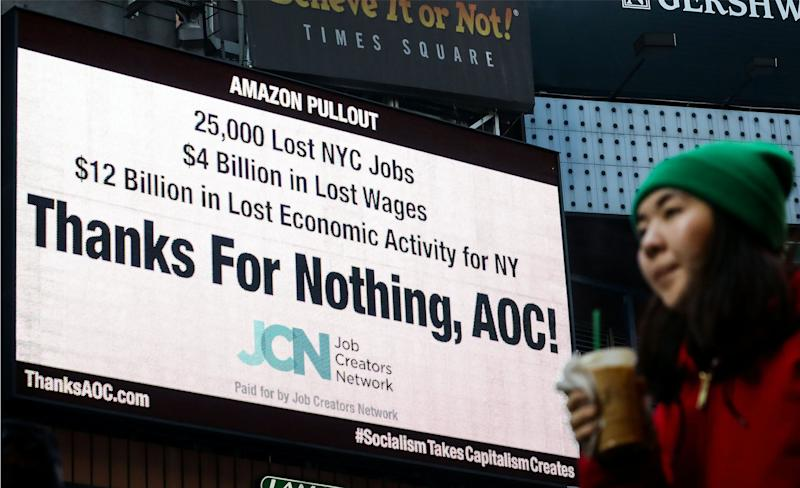 "A woman passes by an electronic billboard in Times Square displaying, ""Thanks For Nothing, AOC!"", referencing U.S. Rep. Alexandria Ocasio-Cortez (D-NY) and the pullout of Amazon's HQ 2 in New York City, U.S., February 21, 2019. (Photo: REUTERS/Brendan McDermid)"