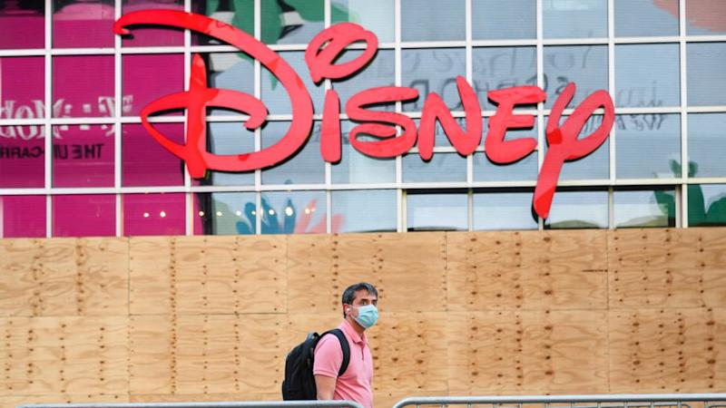 A man in a mask walks past the Disney store in Times Square, New York