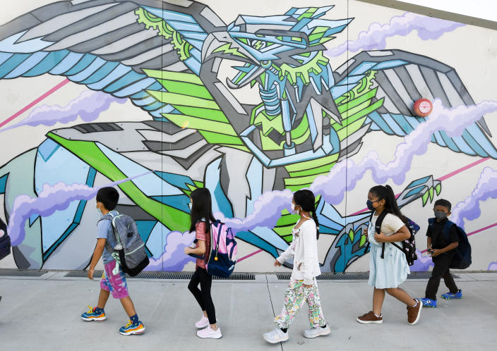 Masked students walk to their classroom on the first day of school at Enrique S. Camarena Elementary School, Wednesday, July 21, 2021, in Chula Vista, Calif. The school is among the first in the state to start the 2021-22 school year with full-day, in-person learning. (AP Photo/Denis Poroy)