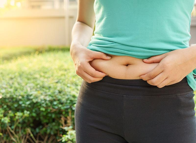 woman holding belly fat