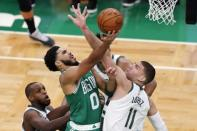 Boston Celtics' Jayson Tatum (0) shoots over Milwaukee Bucks' Brook Lopez (11) during the first half of an NBA basketball game Wednesday, Dec. 23, 2020, in Boston. (AP Photo/Michael Dwyer)