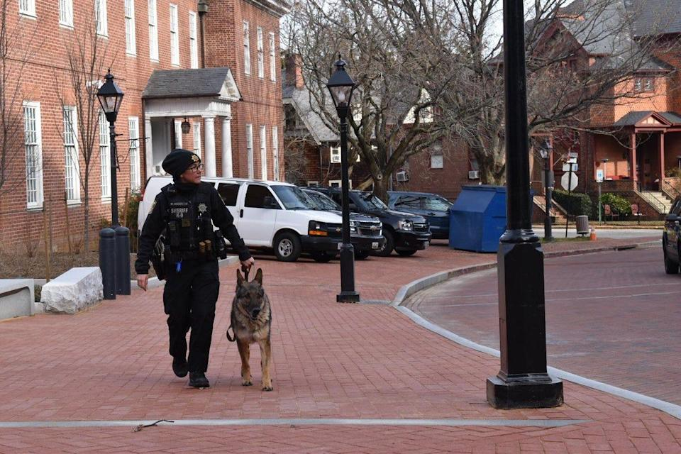 A deputy and K-9 walk near the Maryland Capitol in Annapolis, Md., on Sunday, Jan. 17, 2021. At noon ET, few people were present beyond law enforcement and members of the media.