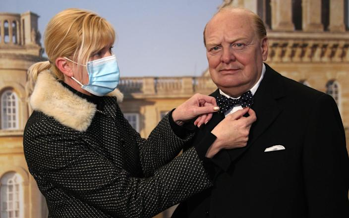 Kate Ballenger, keeper of Palace and Collections at Blenheim Palace, adjusts the bow tie on a waxwork of Winston Churchill by sculptor Jethro Crabbe, which forms part of a new Churchill exhibition at Blenheim Palace in Oxfordshire, as the attraction is prepared for the public ahead of further easing of lockdown restrictions in England - Andrew Matthews/PA