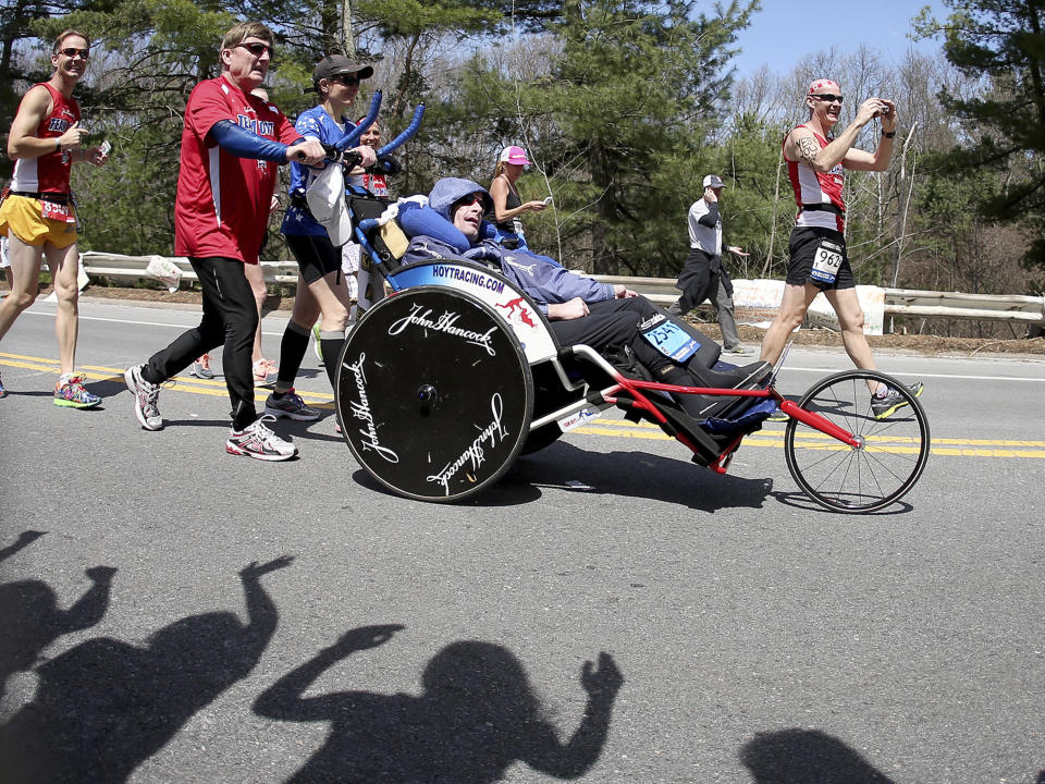 FILE - In this April 21, 2014, file photo, Dick Hoyt, left, pushes his son Rick during the Boston Marathon together as they pass through Wellesley, Mass. Dick Hoyt, who last competed with his son in the Boston Marathon in 2014, has died, the Boston Athletic Association announced Wednesday, March 17, 2021. He was 80. (AP Photo/Mary Schwalm, File)