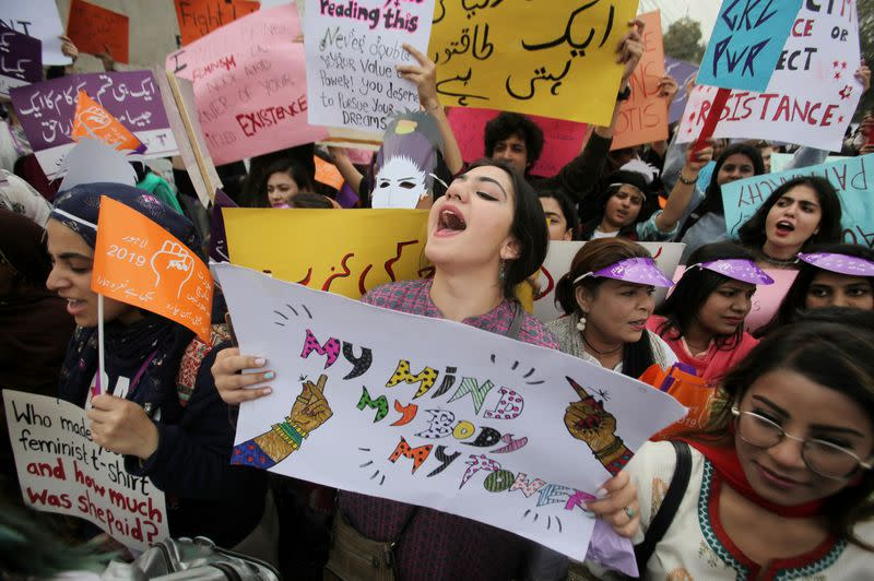 FILE PHOTO: Woman carries a sign and chants slogans during a rally to mark International Women's Day in Lahore