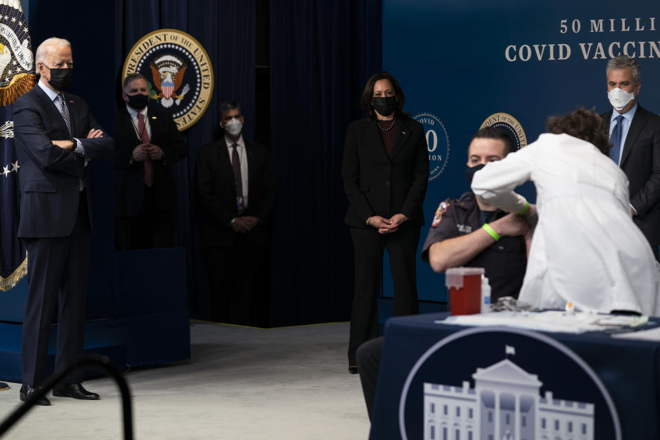 President Joe Biden looks on as DC firefighter and EMT Corey Hamilton receives a vaccination, during an event to commemorate the 50 millionth COVID-19 shot, in the South Court Auditorium on the White House campus, Thursday, Feb. 25, 2021, in Washington. Vice President Kamala Harris and White House COVID-19 Response Coordinator Jeff Zients look on. (AP Photo/Evan Vucci)