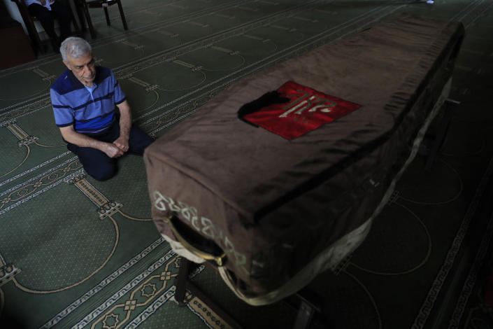 The father of Ibrahim Harb, 35, a Lebanese man who was critically injured in the massive explosion at Beirut's port last year and who died on Monday nearly 14 months after the blast, prays at a mosque at his son's coffin in Beirut, Lebanon, Tuesday, Sept. 28, 2021. On Aug. 4, 2020, hundreds of tons of ammonium nitrate, a highly explosive material used in fertilizers, ignited after a massive fire at the port. The death brings to at least 215 the number of people who have been killed by the blast, according to official records. (AP Photo/Hussein Malla)