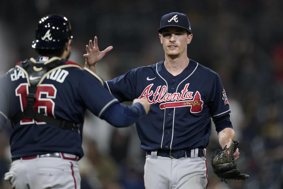 Atlanta Braves starting pitcher Max Fried, right, celebrates with catcher Travis d'Arnaud after throwing a complete game as the Braves defeated the San Diego Padres 4-0 in the baseball game Friday, Sept. 24, 2021, in San Diego. (AP Photo/Gregory Bull)