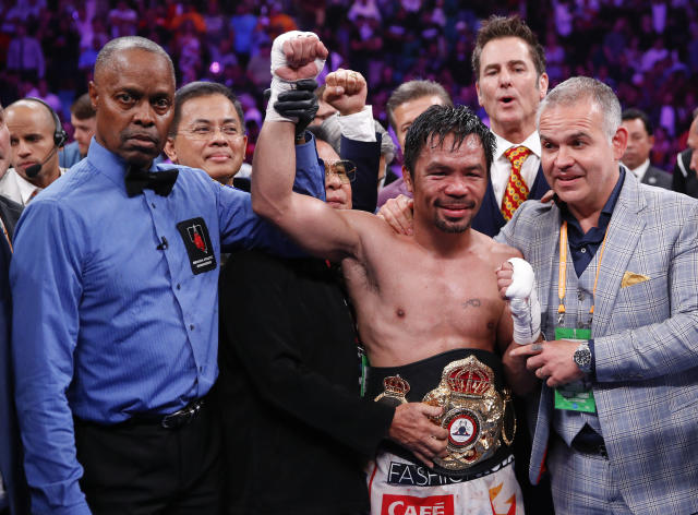 Manny Pacquiao, center, reacts as referee Kenny Bayless holds up his hand signaling his victory over Keith Thurman in a welterweight title fight Saturday, July 20, 2019, in Las Vegas. Pacquiao won by split decision. (AP Photo/John Locher)
