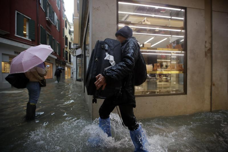 FILE - In this Friday, Nov. 15, 2019 file photo, a man holds his luggage as he wades his way through water in Venice, Italy. Venice's hoteliers association estimates that the city's hotels suffered about 30 million euros ($34 million) worth of structural damage during November's floods. The overall losses though are higher when the lower revenues that local hotels have reported in the wake of the surging high tides are added in. (AP Photo/Luca Bruno, File)