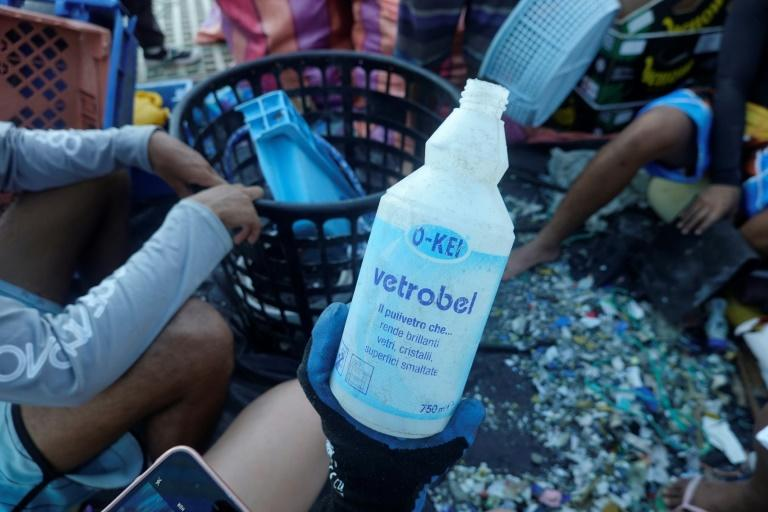 A volunteer holds a detergent plastic bottle collected on Isabela Island in the Galapagos archipelago in February 2019