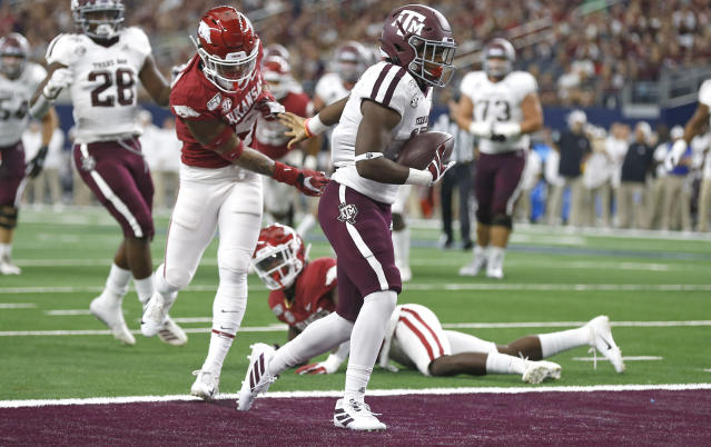 Texas A&M wide receiver Ainias Smith carries the ball across the goal line past Arkansas defensive back Greg Brooks Jr. (9) to score a touchdown during the first half of an NCAA college football game Saturday, Sept. 28, 2019, in Arlington, Texas. (AP Photo/Ron Jenkins)
