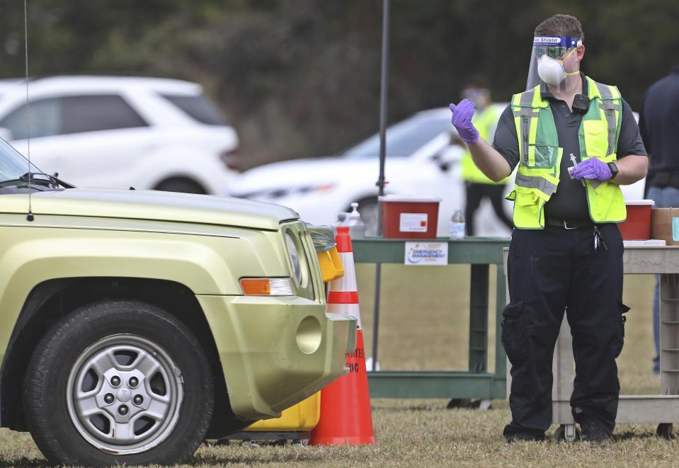 A health worker directs a vehicle before administering a COVID-19 vaccine to one of about 300 people to get vaccinated, Wednesday, Dec. 30, 2020, at the Manatee County Public Safety Center in Bradenton, Fla. (Scott Keeler/Tampa Bay Times via AP)
