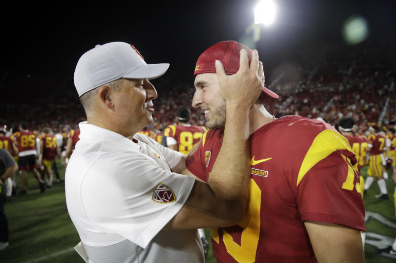 Southern California coach Clay Helton, left, hugs quarterback Matt Fink after the team's 30-23 win over Utah in an NCAA college football game Friday, Sept. 20, 2019, in Los Angeles. (AP Photo/Marcio Jose Sanchez)