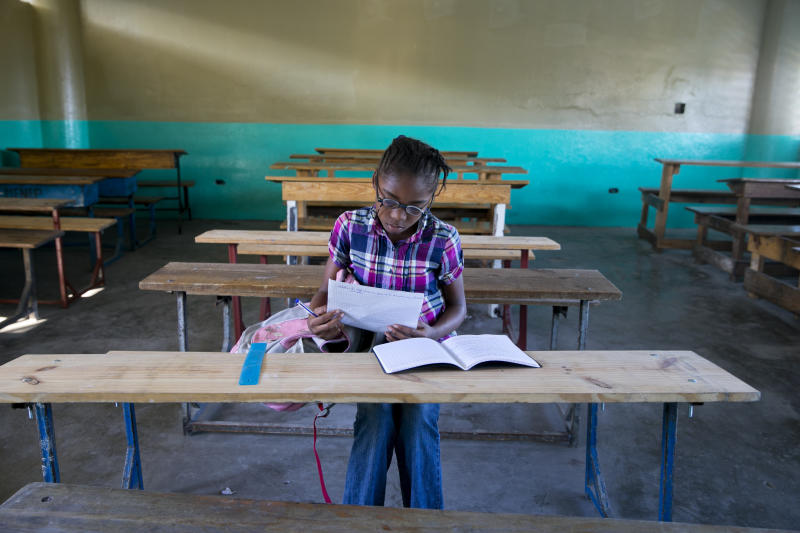 A lone student looks over papers as she waits for her teacher to arrive at the Lycée school, which reopened about a week earlier than other schools in Petion-Ville, Haiti, Thursday, Nov. 28, 2019. Some Haitian children have begun to return to school after classes halted during months of violent unrest. (AP Photo/Dieu Nalio Chery)