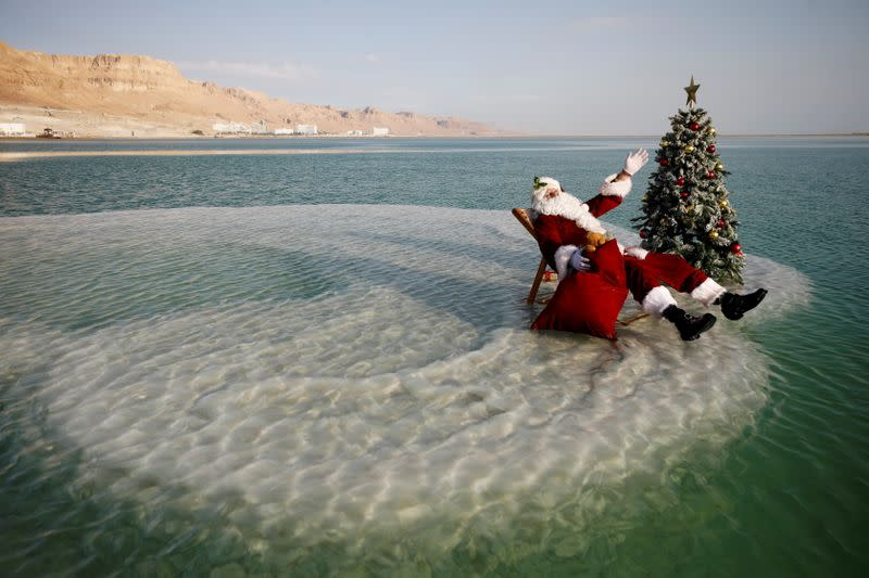 Issa Kassissieh, wearing a Santa Claus costume, sits next to a Christmas tree on a salt formation in the Dead Sea, in an event organised by Israel's tourism ministry, as Israel gears up for the holiday season, amid COVID-19 crisis, near Ein Bokeq