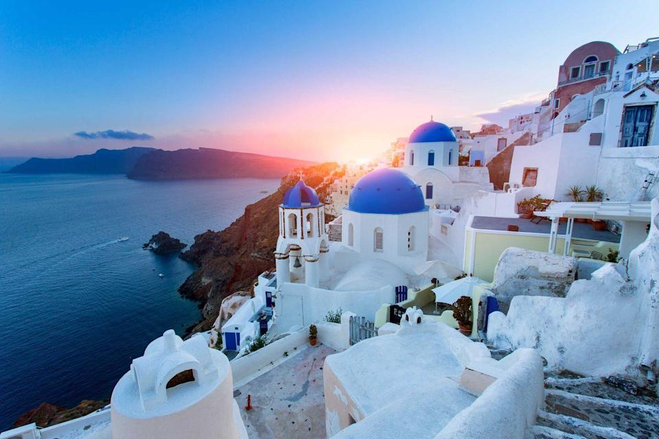 <p>Blue domed churches in a picturesque village at sunset in Santorini, Greece.</p>