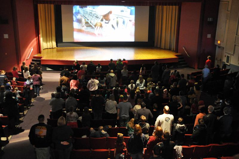 "Some 250 people stand for the playing of the national anthem ahead of a showing of ""Hotel Transylvania"" inside the theater at South Dakota's Ellsworth Air Force Base on its last day of operation, Saturday, Jan. 19, 2013. The Army and Air Force Exchange Service theater serving airmen and their families is one of 60 across the globe that's closing because it's too expensive to switch from 35 millimeter film prints to an all-digital projection format. (AP Photo/Dirk Lammers)"
