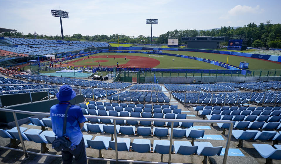A steward watches from the empty grandstands during the softball game between Japan and Australia at the 2020 Summer Olympics, Wednesday, July 21, 2021, in Fukushima, Japan. (AP Photo/Jae C. Hong)