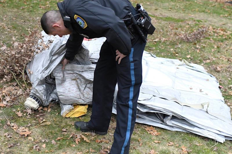 A police officer inspects an evacuation slide that fell from a jet into the garden of a home in Milton: AP