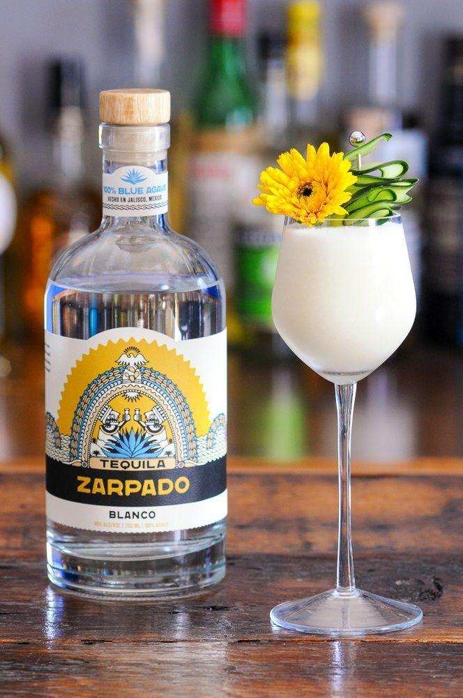 """<p>For a white drink that's not too heavy for summer, rely on a combo of cream of coconut and cooling cucumber. Top with a red flower for a look that skews a little more patriotic.</p><p><strong><em>Ingredients</em></strong><br>2 ounces <a href=""""https://tequilazarpado.com"""" rel=""""nofollow noopener"""" target=""""_blank"""" data-ylk=""""slk:Tequila Zarpado Blanco, or whatever you have on hand."""" class=""""link rapid-noclick-resp"""">Tequila Zarpado Blanco, or whatever you have on hand.<br></a>1 ounce lime juice<br>½-ounce cream of coconut<br>2 slices of cucumber<br>2 dashes cucumber bitters</p><p><strong><em>Method</em></strong><br>Muddle cucumber with lime juice in a shaker. Add in tequila, cream of coconut, and cucumber bitters with ice. Shake to combine and double strain into a glass. Garnish with cucumber ribbons or a slice of cucumber and a flower. </p>"""