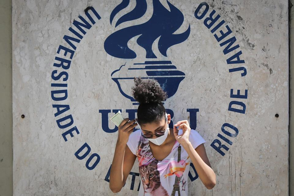 RIO DE JANEIRO, BRAZIL - JANUARY 17:  A student adjusts her protective mask as waiting at the Rio de Janeiro State University (UERJ) for the National High School Exam (ENEM) on January 17, 2021 in Rio de Janeiro, Brazil. Despite 15 Brazilian states showing an increase in the number of deaths from Coronavirus (Covid-19), the government maintained the exam and 5.7 million candidates are confirmed.  (Photo by Andre Coelho/Getty Images)
