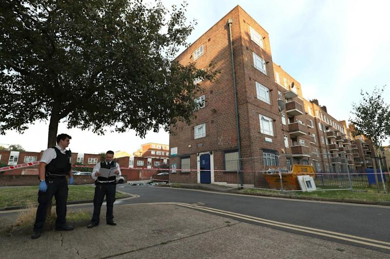 Police officers stand outside Landor House in Camberwell (PA)