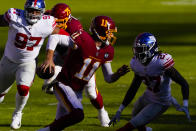 Washington Football Team quarterback Alex Smith (11) runs to avoid being tackled by New York Giants cornerback Isaac Yiadom (27) in the first half of an NFL football game, Sunday, Nov. 8, 2020, in Landover, Md. (AP Photo/Susan Walsh)
