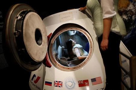 A woman wearing a prototype of Stemrad's new protective vest, Astrorad, sits inside Russian spacecraft, Excalibur-Almaz Space Capsule, during a demonstration for Reuters, at Madatech, National Museum of Science Technology and Space in Haifa, Israel