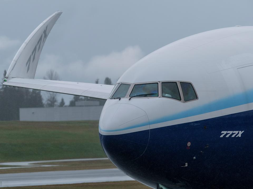 A Boeing 777X preparing for its first test flight amid bad weather.
