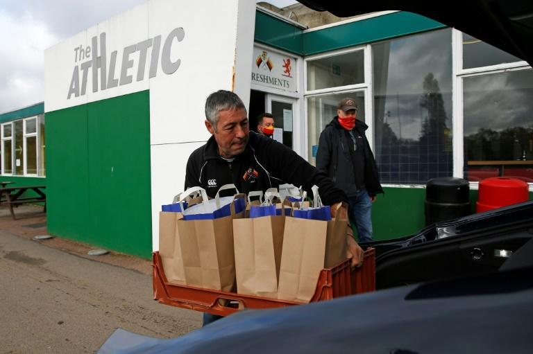 Volunteers from Richmond Rugby load bags of meals into a car before delivering them to local children in Twickenham during school vacation when needy youngsters are not geeting free meals at school