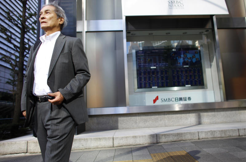 A man walks in front of a securities firm in Tokyo, Friday, Nov. 8, 2013. Asian stocks tracked losses in the U.S. on renewed concern the Federal Reserve will start scaling back stimulus earlier than expected after a report showed that the U.S. economy grew faster than predicted. (AP Photo/Junji Kurokawa)