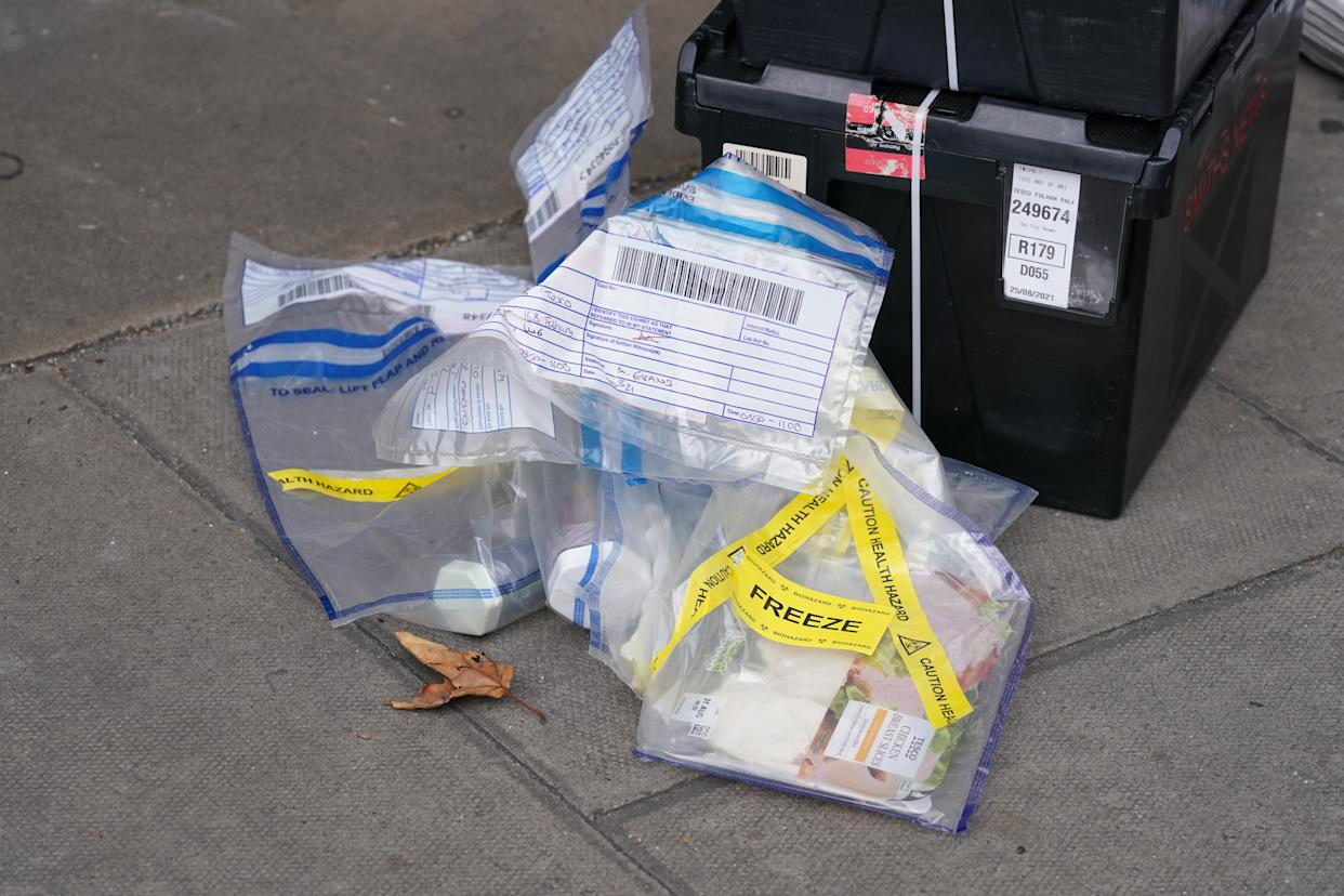 Evidence bags marked as a health hazard and containing produce outside the Tescoe Express store on Fulham Palace Road, west London, which has been closed and a crime scene put in place after a man was arrested on suspicion of contaminating food with a syringe. Police were called on Wednesday evening to a man shouting abuse at people in the street and three supermarkets Tesco Express, Little Waitrose and Sainsbury's Local - have been closed for investigation. Picture date: Thursday August 26, 2021.