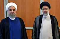 Raisi (R) stands with Iran's outgoing president Hassan Rouhani during his inauguration ceremony