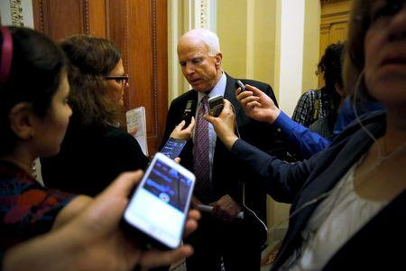 McCain speaks with a reporter after the weekly Republican caucus luncheon at the U.S. Capitol in Washington
