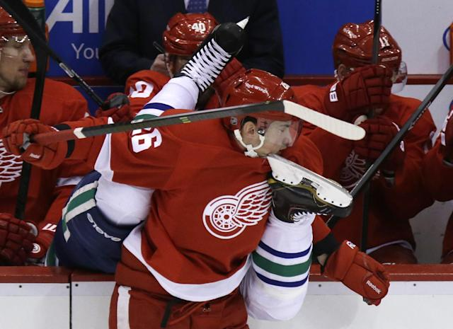 Detroit Red Wings right wing Tomas Jurco (26) checks Vancouver Canucks defenseman Alexander Edler of Sweden into the Red Wings bench during the first period of an NHL hockey game in Detroit, Monday, Feb. 3, 2014. (AP Photo/Carlos Osorio)