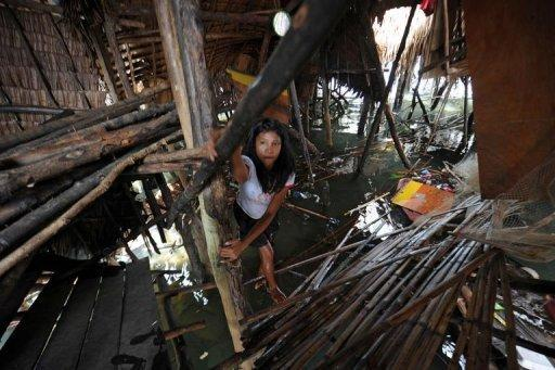 A resident climbs up the collapsed floor of her house