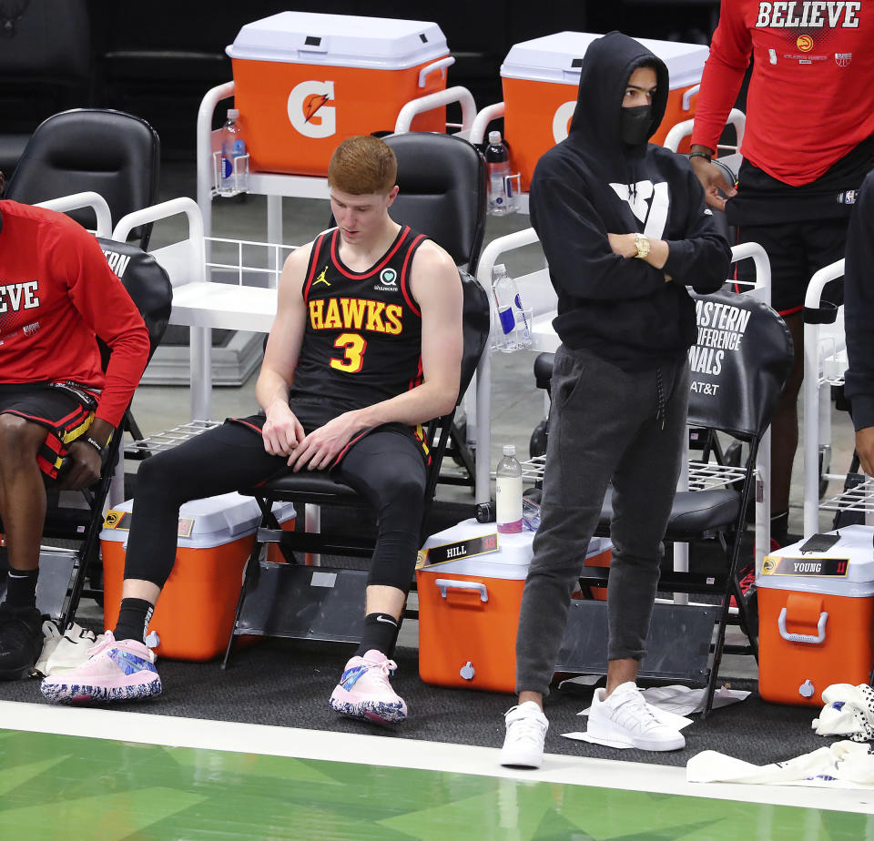 Atlanta Hawks guards Kevin Huerter, left, and Trae Young, who did not play, watch from the bench in the final minute of the team's loss to the Milwaukee Bucks in Game 5 of the Eastern Conference finals in the NBA basketball playoffs Thursday, July 1, 2021, in Milwaukee. (Curtis Compton/Atlanta Journal-Constitution via AP)