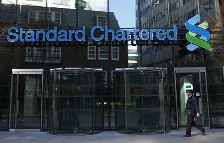 FILE PHOTO: A man walks past the head office of Standard Chartered bank in the City of London February 27, 2015. REUTERS/Eddie Keogh