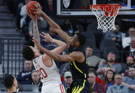 Oregon's Francis Okoro, right, tries to block a shot by Utah's Timmy Allen during the second half of an NCAA college basketball game in the quarterfinals of the Pac-12 men's tournament Thursday, March 14, 2019, in Las Vegas. (AP Photo/John Locher)