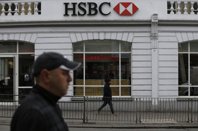 People walk past a branch of the HSBC bank in London, Wednesday, May 15, 2013, after the bank announced 2 to 3 billion US dollars in new cuts as it continues to trim its global empire. Europe's biggest bank by market value, HSBC announced a doubling of its profit earlier this month as it reaped the benefits of recent restructuring, trimming around 40,000 jobs from a workforce of about 300,000 since 2011, but the new cost cutting is widely expected to translate into additional layoffs. (AP Photo/Lefteris Pitarakis)