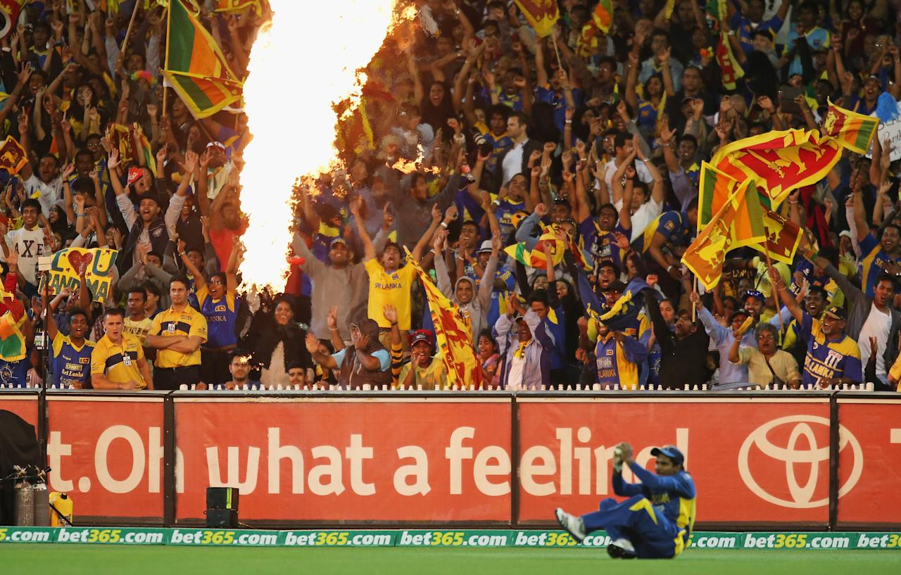 MELBOURNE, AUSTRALIA - JANUARY 28:  Sri Lankan fans celebrate after Kushal Janith Perera of Sri Lanka took a catch on the boundary to dismiss George Bailey of Australia during game two of the Twenty20 International series between Australia and Sri Lanka at the Melbourne Cricket Ground on January 28, 2013 in Melbourne, Australia.  (Photo by Scott Barbour/Getty Images)