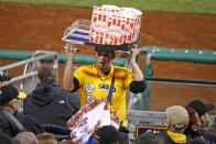 FILE - In this April 29, 2016, file photo, a popcorn and Cracker Jack vendor sells his wares in the stands at PNC Park during a baseball game between the Pittsburgh Pirates and the Cincinnati Reds in Pittsburgh. There will be empty ballparks on what was supposed to be Major League Baseball's opening day. There will be no vendors in the stands selling peanuts and Cracker Jack for baseball fans ready to come back. The start of the MLB regular season is indefinitely on hold because of the coronavirus pandemic. (AP Photo/Gene J. Puskar, FIle)