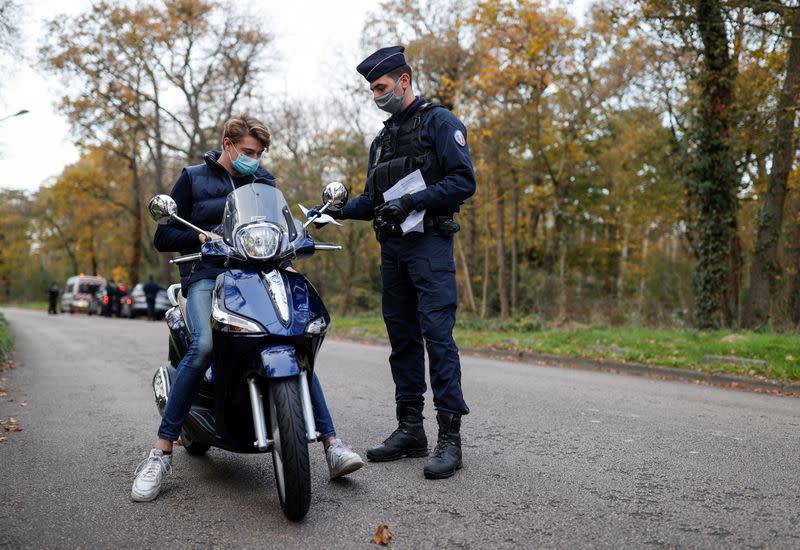 French police officers conduct a control to check exemption certificates in Paris