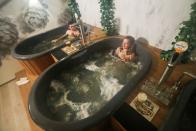Customers enjoy a beer while relaxing in a jacuzzi full of hot water and a mixture of ingredients used to make beer at the Good Beer Spa in Brussels