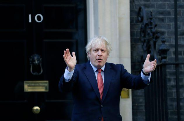 Boris Johnson applauds on the doorstep of 10 Downing Street in London during the weekly Clap for our Carers.